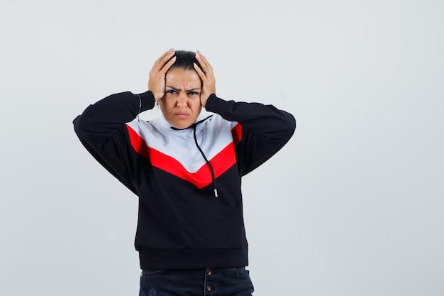 Giovane donna che tiene le mani sulla testa, avendo mal di testa in maglione e jeans neri e guardando infastidito. vista frontale.