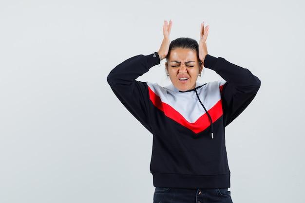 Giovane donna che tiene le mani sulla testa, avendo mal di testa in maglione e jeans neri e guardando esausto, vista frontale.