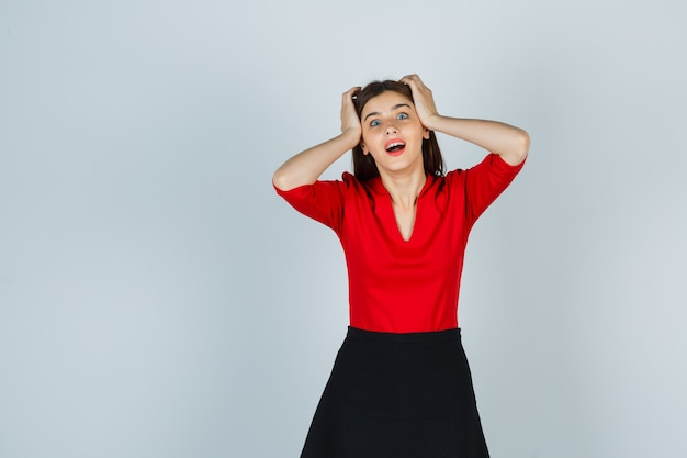 Young woman holding hands on head in red blouse, black skirt and looking surprised
