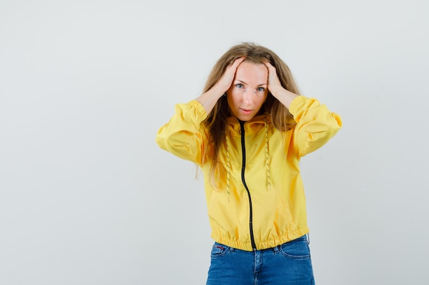 Young woman holding hands on head in yellow bomber jacket and blue jean and looking attractive , front view.