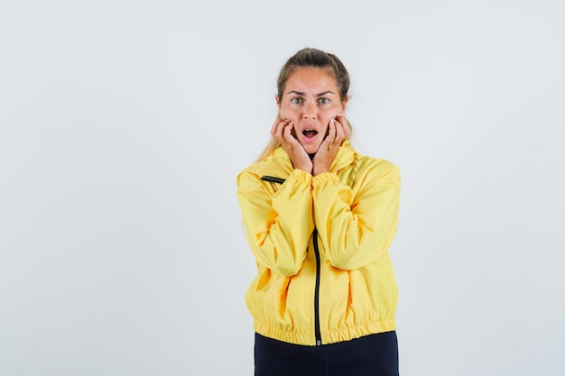 Young woman holding hands on her dropped jaw in yellow raincoat and looking nervous