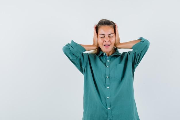 Giovane donna che tiene le mani sulle orecchie in camicia blu e sembra riluttante
