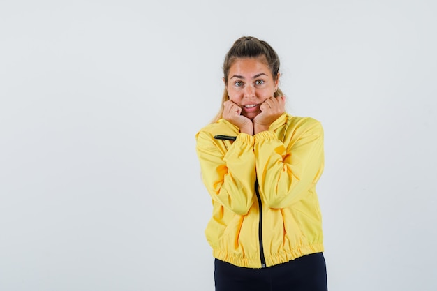 Young woman holding hands on her jaw in yellow raincoat and looking troubled