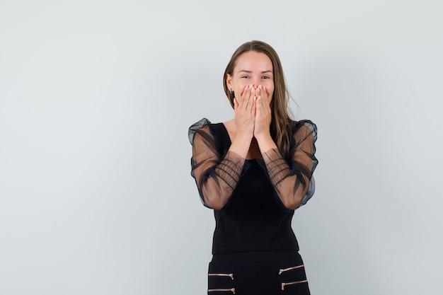 Giovane donna che si tiene per mano sulla sua bocca mentre ride in camicetta nera e sembra allegra