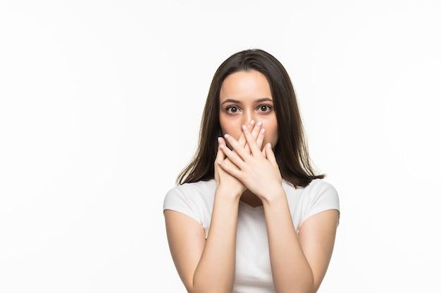 Giovane donna che si tiene per mano sulla bocca su un bianco