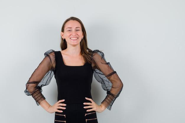 Giovane donna che tiene le mani sulla sua vita mentre sorride in camicetta nera e sembra hale