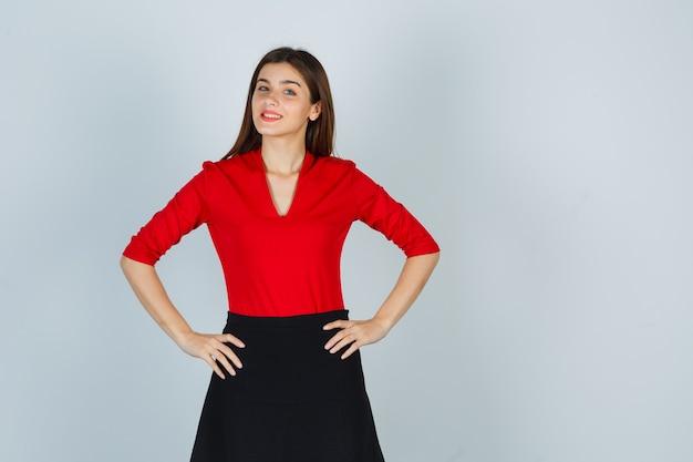 Giovane donna che tiene le mani sui fianchi in camicetta rossa, gonna nera e sembra allegra