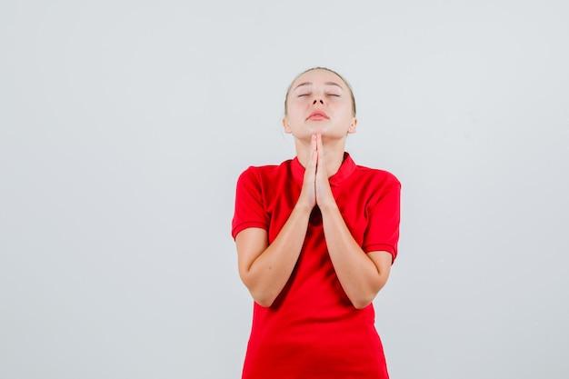 赤いtシャツでジェスチャーを祈って手をつないで平和に見える若い女性
