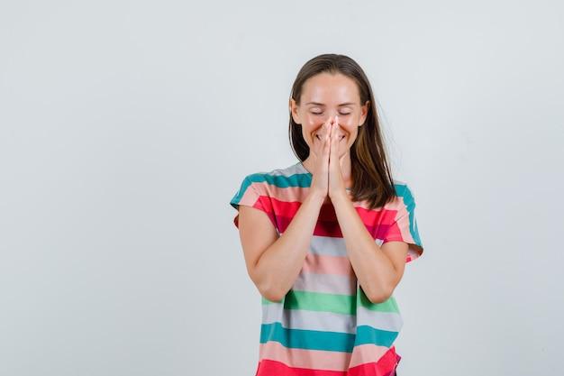 Tシャツで祈りのジェスチャーで手をつないで、感謝の気持ちを表す若い女性、正面図。