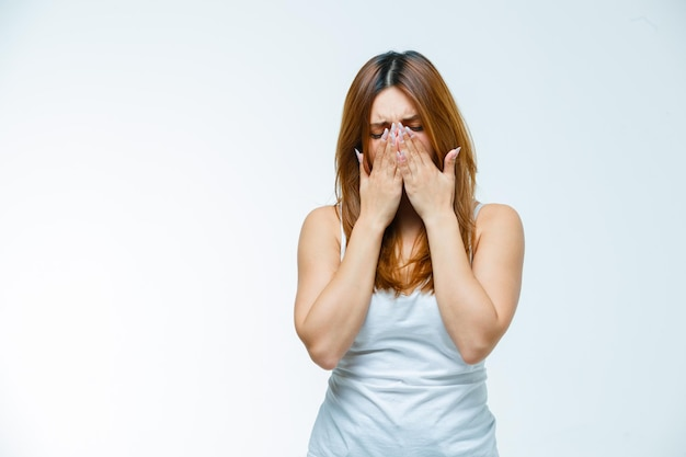 Giovane donna che si tiene per mano sulla bocca mentre piange