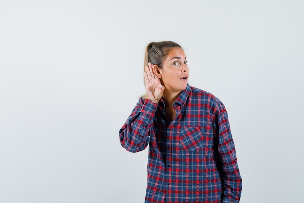 Young woman holding hands near ear to hear something in checked shirt and looking happy