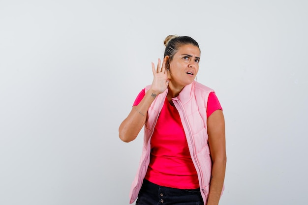 Giovane donna che si tiene per mano vicino all'orecchio per sentire qualcosa in maglietta e giacca rosa e sembra concentrata