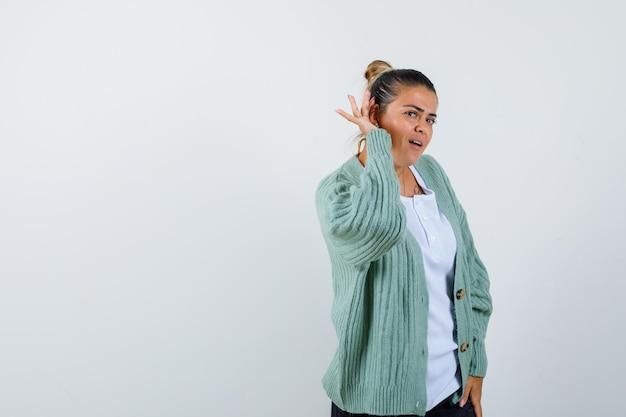 Young woman holding hands near ear to hear something in white t-shirt and mint green cardigan and looking focused