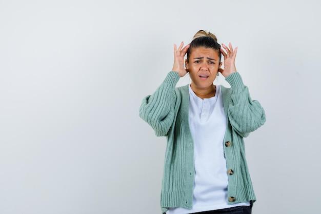 Giovane donna che si tiene per mano vicino all'orecchio in camicia bianca e cardigan verde menta e sembra tormentata