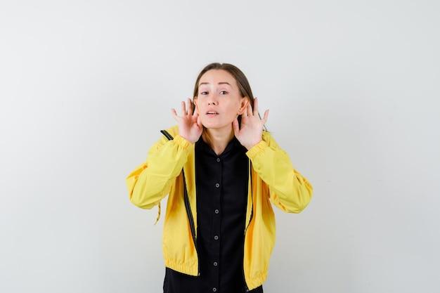 Giovane donna che si tiene per mano vicino alle orecchie per ascoltare