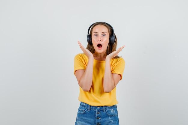 Tシャツ、ショートパンツ、ヘッドフォンで顔の近くで手をつないで、怖がって見える若い女性