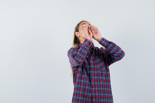 チェックシャツを着て誰かを呼び出し、集中して見えるように口の近くで手をつないでいる若い女性