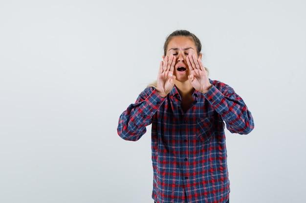 チェックのシャツを着て誰かを呼び出し、真剣に見えるように口の近くで手をつないでいる若い女性