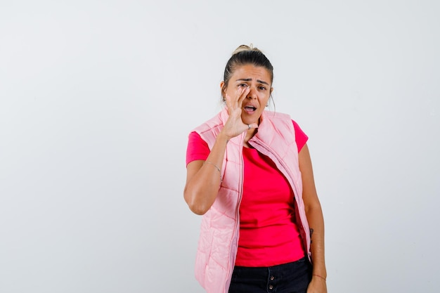 ピンクのtシャツとジャケットで誰かを呼び出し、集中して見えるように口の近くで手をつないでいる若い女性