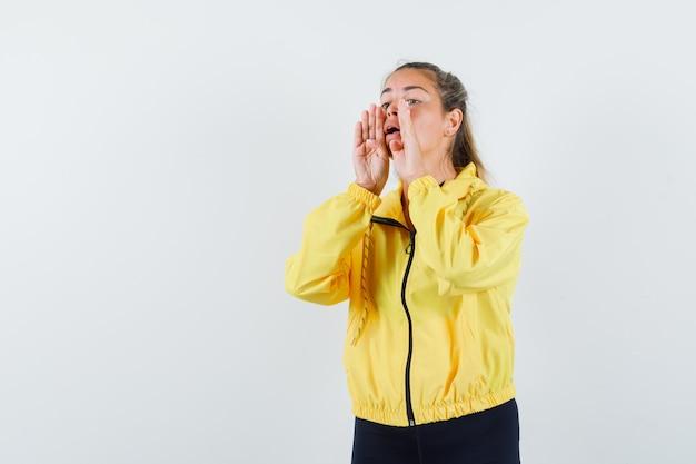Молодая женщина, взявшись за руки возле рта, зовет кого-то в желтой куртке-бомбардировщике и черных штанах и выглядит мило