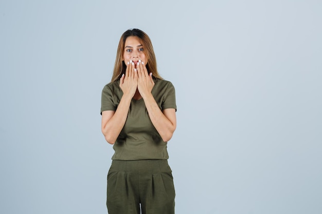 Молодая женщина, взявшись за руки возле рта в футболке, штанах и выглядя удивленно. передний план.