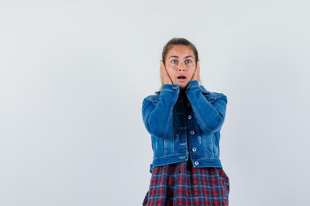 Молодая женщина, взявшись за руки в рубашке, куртке и с тревогой глядя на щеки, вид спереди.