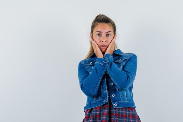 Молодая женщина, взявшись за щеки в рубашке, куртке и выглядя нежной, вид спереди.