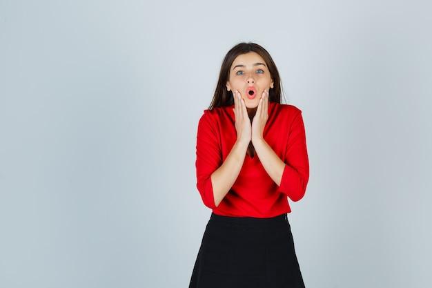 Молодая женщина, держась за щеки, держа рот широко открытым в красной блузке