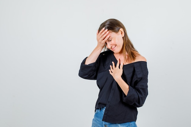 シャツ、ショートパンツの正面図で胸と額に手をつないでいる若い女性。