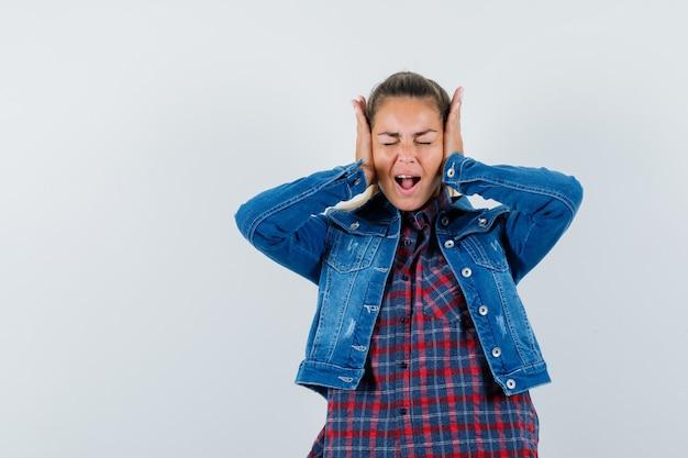 젊은 여자는 셔츠, 재킷에 귀에 손을 잡고 염증, 전면보기를 찾고.