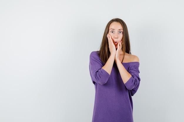 紫のシャツで顔に手をつないで、ショックを受けた、正面図を探している若い女性。