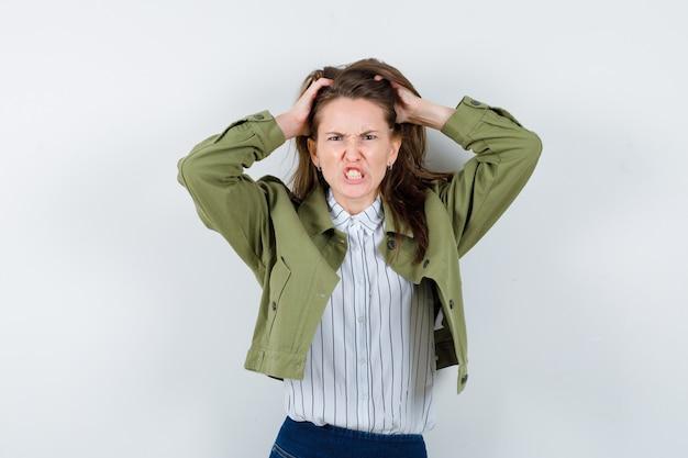 頭に手をつないで、シャツの歯を食いしばって、緊張している若い女性。正面図。