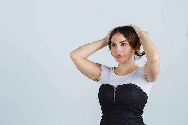 Молодая женщина, взявшись за руки на голове, думает о чем-то