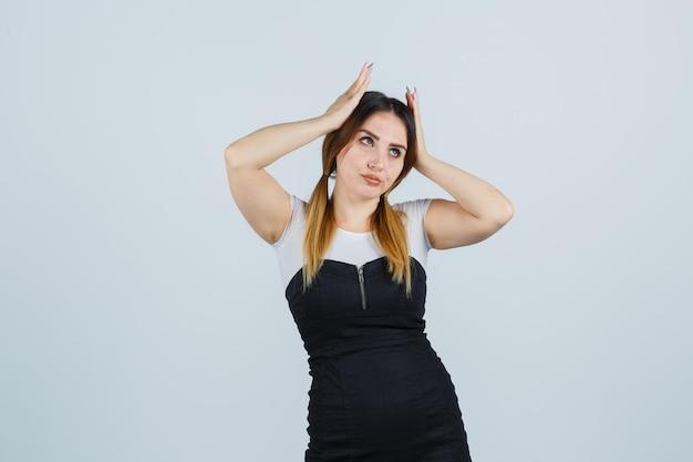 Молодая женщина, взявшись за руки за голову