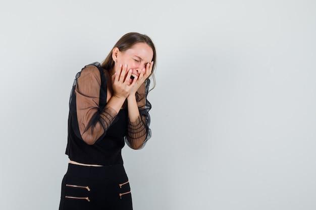 검은 블라우스에 외치고 복잡해 보이는 동안 그녀의 얼굴에 손을 잡고 젊은 여자