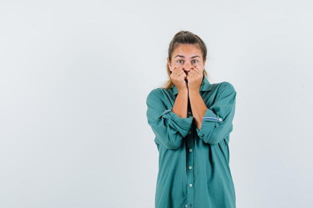 Молодая женщина, держась за рот в синей рубашке и с тревогой глядя