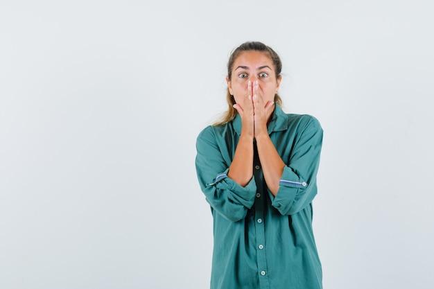 青いシャツを着て目を大きく開き、恐怖を感じながら口に手をつないでいる若い女性