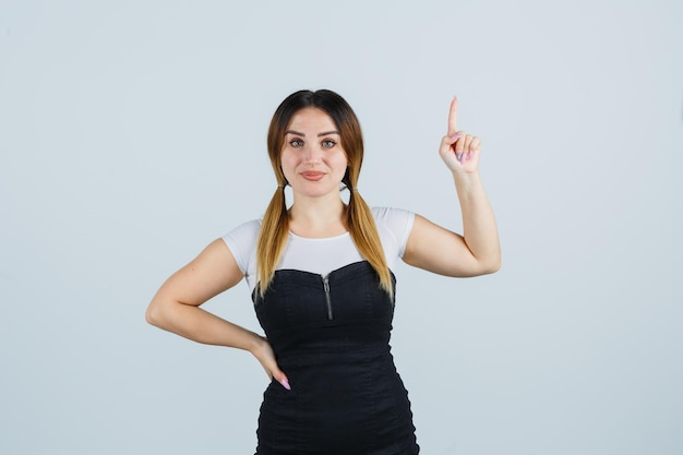 腰に手をつないで、ユーレカジェスチャーで人差し指を指す若い女性