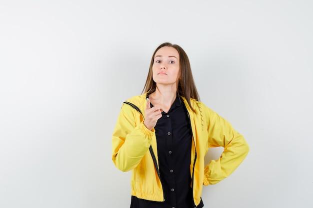 腰に手をつないで、警告ジェスチャーで人差し指を上げる若い女性