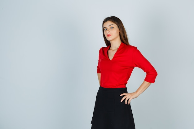 Молодая женщина, держащая руки на бедрах в красной блузке, черной юбке и уверенная в себе