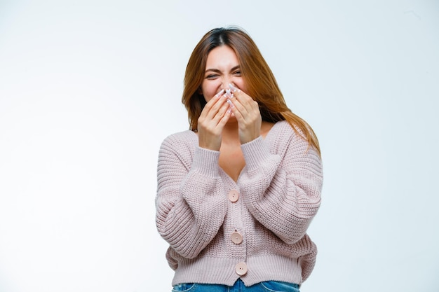 Молодая женщина, держась за рот во время смеха