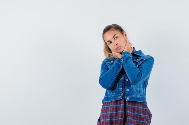 셔츠, 재킷에 목에 손을 잡고 사려 깊은 찾고 젊은 여자. 전면보기.