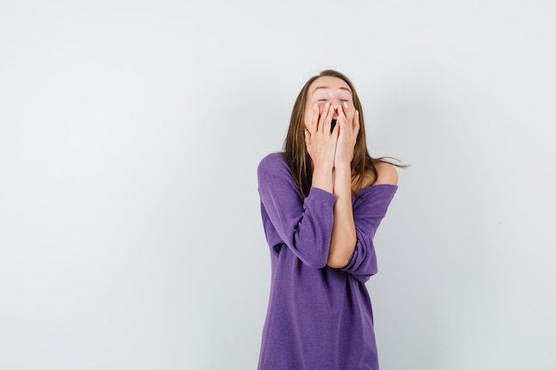 Молодая женщина, держащая руки на открытом рту в фиолетовой рубашке и выглядящая счастливой. передний план.