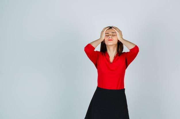Молодая женщина, держащая руки на висках в красной блузке, черной юбке и выглядящая взволнованной