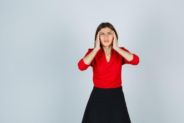 Молодая женщина, держащая руки на висках в красной блузке, черной юбке и обеспокоенная