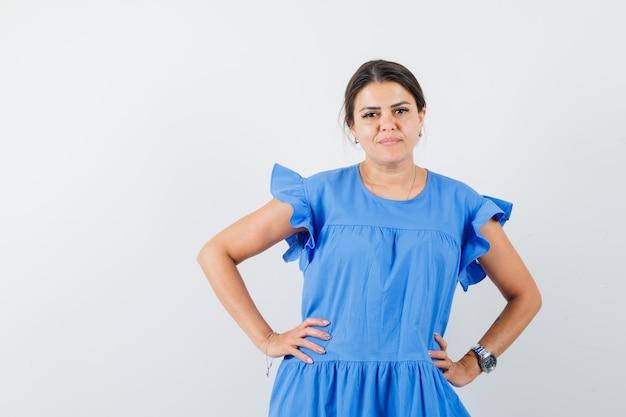Молодая женщина, держащая руки на талии в синем платье и выглядящая уверенно