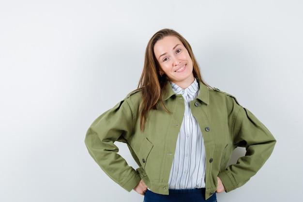 シャツ、ジャケットで腰に手をつないで、自信を持って見える若い女性。正面図。