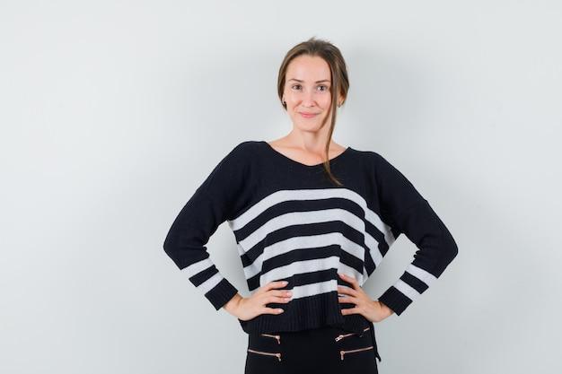 Молодая женщина, держащая руки на талии в полосатом трикотажном белье и черных брюках, выглядит уверенно