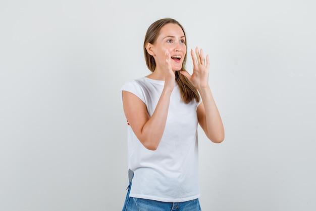 Giovane donna che tiene le mani per gridare in maglietta, pantaloncini e guardando allegra