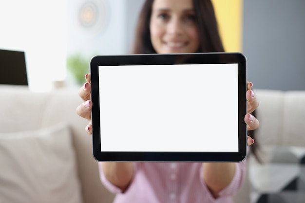 Young woman holding in hands and showing digital tablet closeup. sale of computer equipment and electronics concept
